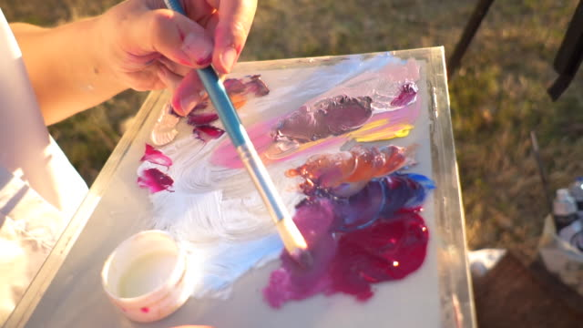 young beautiful girl painting outdoors - easel stock videos and b-roll footage