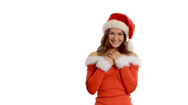 vídeos de stock e filmes b-roll de jovem menina bonita recebe um presente em uma santa claus - chapéu do pai natal