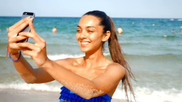 young beautiful girl taking selfies on the beach - photo shooting stock videos and b-roll footage