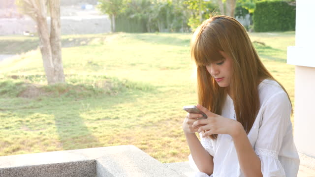 Young Beautiful girl texting a smartphone