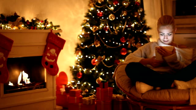 young beautiful girl using digital tablet on christmas night - stockings stock videos & royalty-free footage
