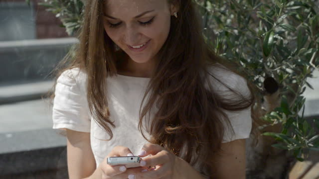 stockvideo's en b-roll-footage met young beautiful girl with a smartphone in the city - witte jurk