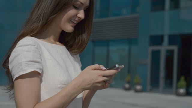 vídeos de stock e filmes b-roll de jovem linda menina com um smartphone na cidade - vestido branco
