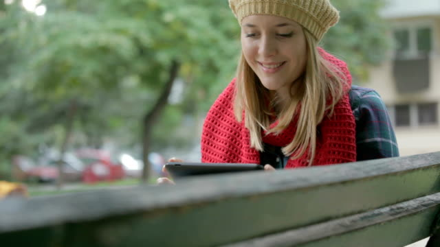 Young beautiful girl with tablet PC sitting on bench