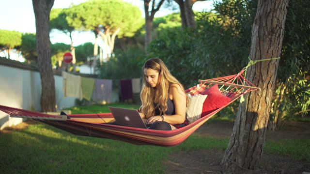Young beautiful girl working with her laptop in the hammock