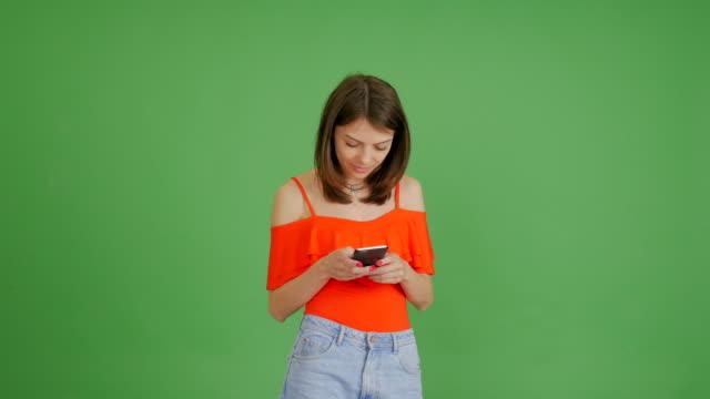 vidéos et rushes de jeune belle fille écrit un message sur le téléphone sur un fond vert - objet ou sujet détouré