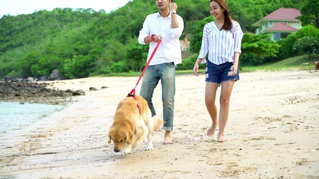 Jonge mooie verliefde paar spelen met hun hond aan zee.