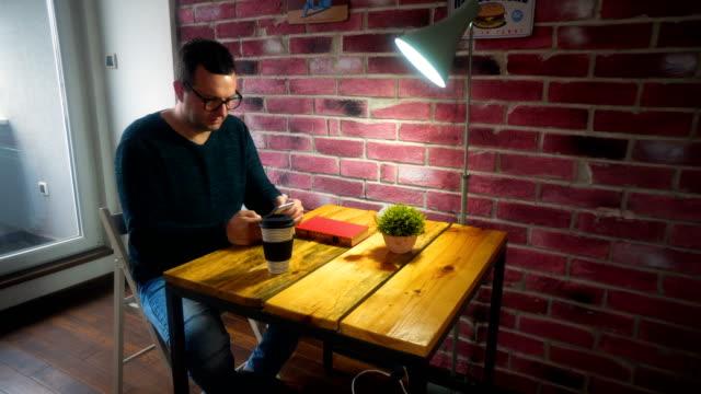 vídeos de stock e filmes b-roll de young beautiful man sitting and drinks coffee. also he reading a book - óculos de leitura