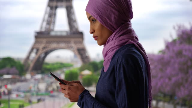 young beautiful muslim woman in paris, france texting near the eiffel tower - france stock videos & royalty-free footage