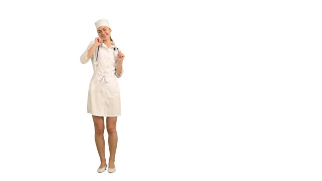 Young beautiful nurse dancing on a white background
