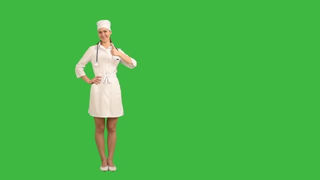 vidéos et rushes de jeune et jolie infirmière représente un espace de copie sur fond vert - doctoresse