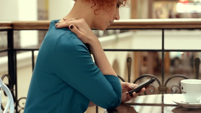 vídeos y material grabado en eventos de stock de pelirrojo joven hermosa mujer sentada en el centro comercial. - sólo mujeres jóvenes