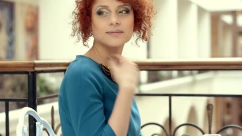 young beautiful redhead woman sitting in the mall. - endast unga kvinnor bildbanksvideor och videomaterial från bakom kulisserna