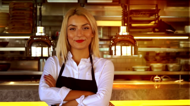 young beautiful waitress in apron standing with arms crossed in cafe or restaurant - fashionable stock videos & royalty-free footage