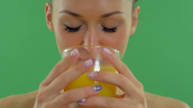 young beautiful woman drinking orange juice