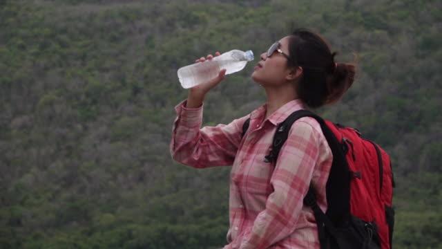 vidéos et rushes de jeune belle femme buvant l'eau de la bouteille à l'extérieur, souriant - joggeuse