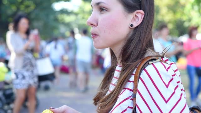 young beautiful woman eating corn