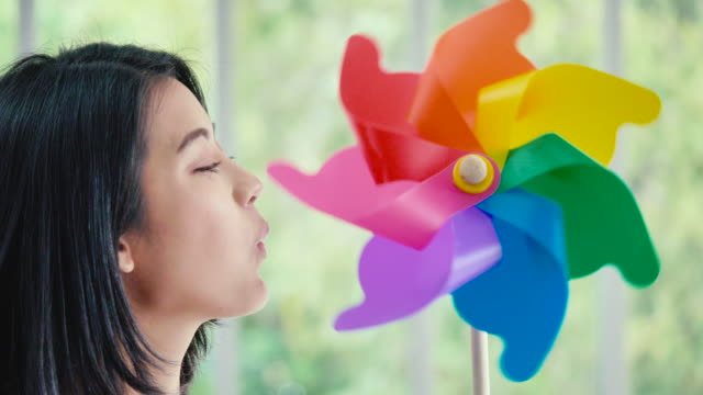 young beautiful woman enjoying and playing with a pinwheel toy. - mill stock videos & royalty-free footage