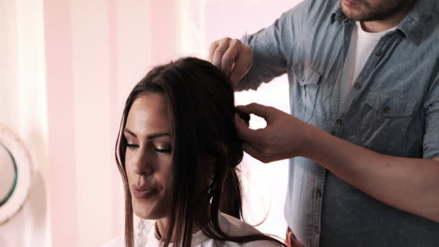 young beautiful woman enjoying while getting her hair styled at hairdresser's. - hair treatment stock videos and b-roll footage