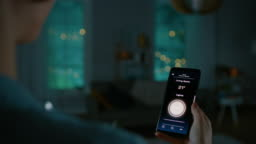 Young Beautiful Woman Gives a Voice Command to a Smart Home Application on Her Smartphone and Lights in the Room are Being Turned On. She Walks and Sits on a Couch. It's a Cozy Evening.