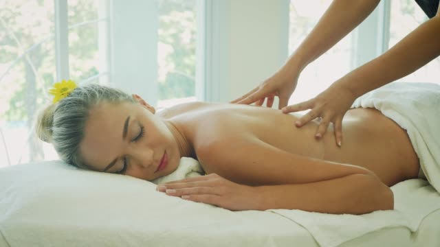 young beautiful woman having a wellness back massage and relaxing in spa salon - massaging stock videos & royalty-free footage