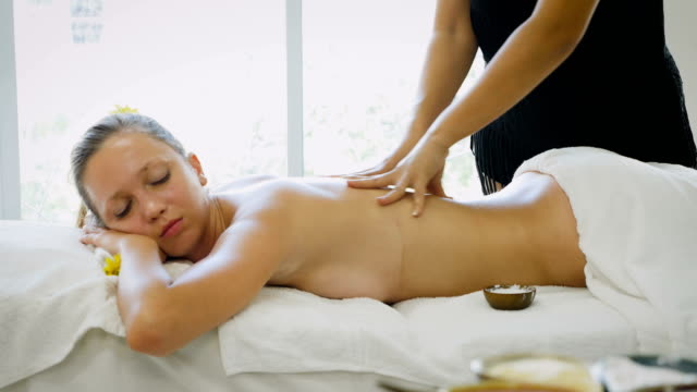 young beautiful woman having a wellness back massage and relaxing in spa salon - health spa stock videos and b-roll footage