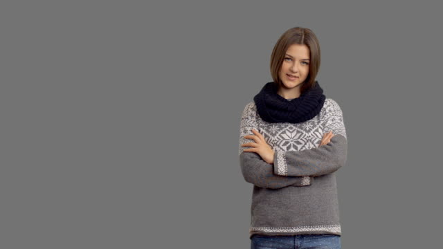 young beautiful woman in a winter sweater on a gray background - gray background stock videos & royalty-free footage
