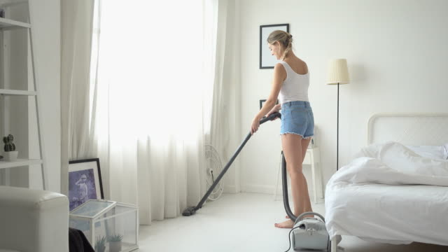 young beautiful woman in casual shirt and shorts vacuum cleaning at her room - cordless phone stock videos & royalty-free footage