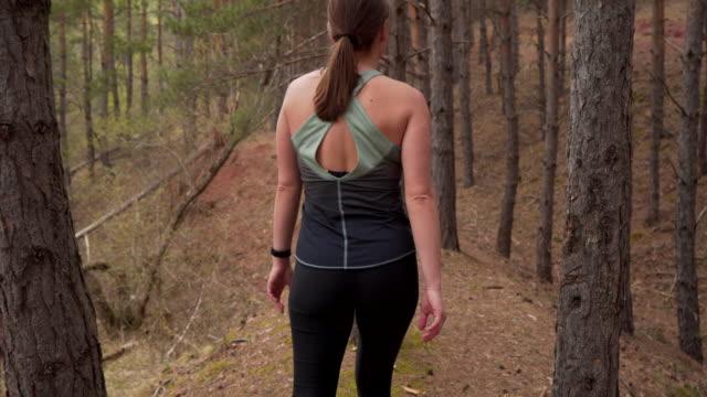 vidéos et rushes de jeune belle femme dans la marche de sportswear - joggeuse