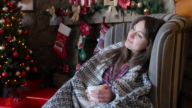 young beautiful woman is drinking tea near the christmas tree - chair stock videos & royalty-free footage