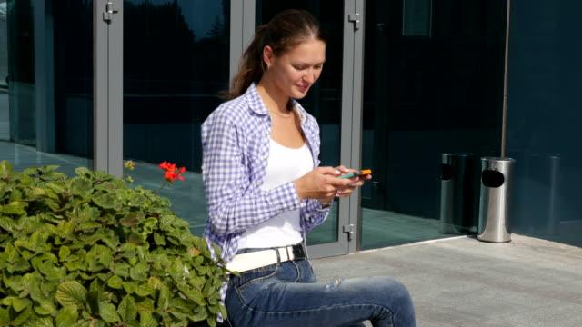 若くてきれいな女性がスマート フォンでメッセージを入力します。 - 特定されない場所点の映像素材/bロール