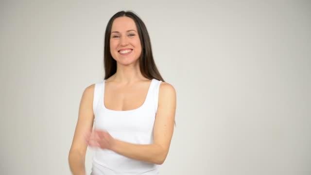 giovane bella donna guardando la telecamera e sorridente - abbigliamento da neonato video stock e b–roll