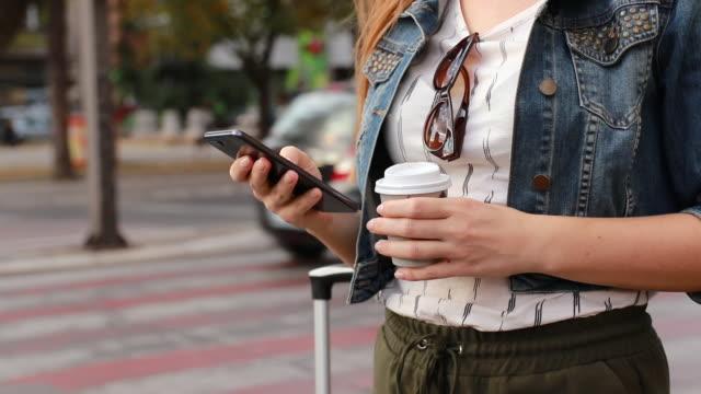 giovane bella donna in cerca di un taxi con un telefono cellulare mentre in piedi sul marciapiede - taxi video stock e b–roll