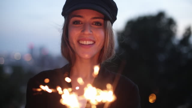 young beautiful woman making a wish with a sparkler - sparkler stock videos & royalty-free footage
