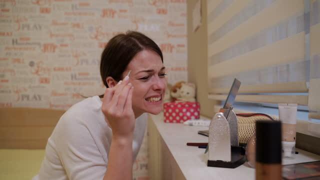 junge schöne frau zupft ihre augenbrauen mit pinzette mit einem schrei des schmerzes - hirnnerv stock-videos und b-roll-filmmaterial