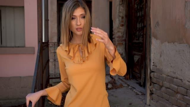 屋外でポーズをとっている若い美しい女性、放棄された家の前で、オレンジ色のドレスで - トルソー点の映像素材/bロール