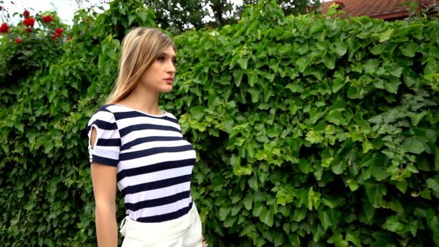 若い美しい女性が屋外でポーズ。スローモーション - トルソー点の映像素材/bロール