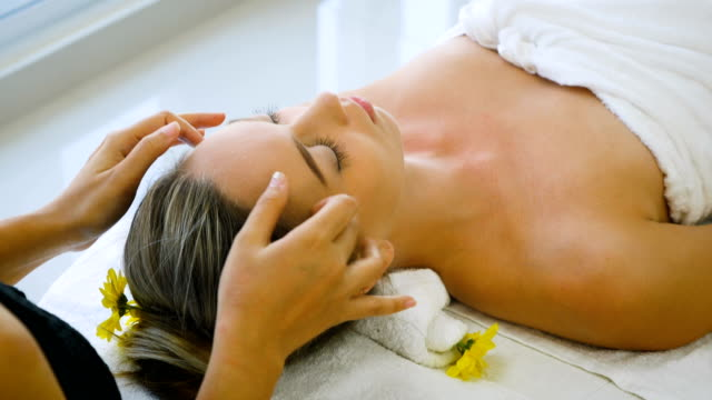 young beautiful woman relaxing in spa salon and receiving head or face massage - beauty treatment stock videos and b-roll footage