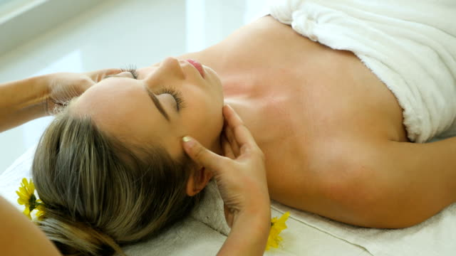 Young beautiful woman relaxing in spa salon and receiving head or face massage