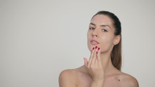 Jovem mulher bonita esfregar máscara facial no rosto