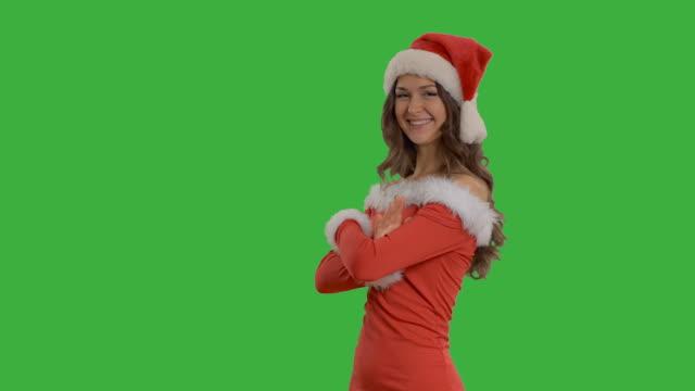 vidéos et rushes de jeune belle femme montre copie espace en chapeau de père noël - robe rouge