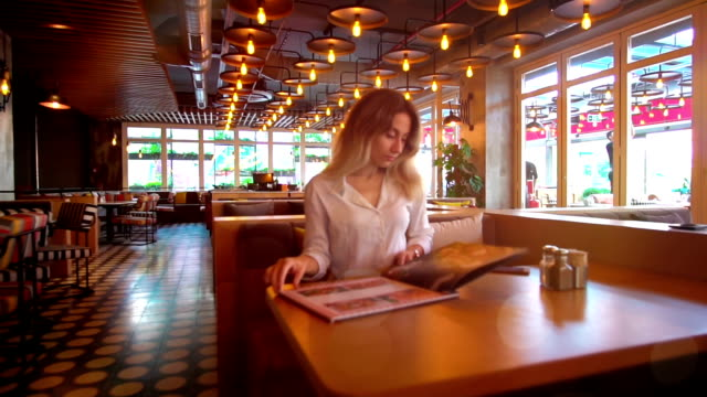 young beautiful woman sitting in a restaurant or a cafe and looking at the menu. - menu stock videos & royalty-free footage