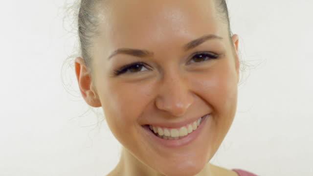 Jovem bela mulher sorridente em um fundo branco