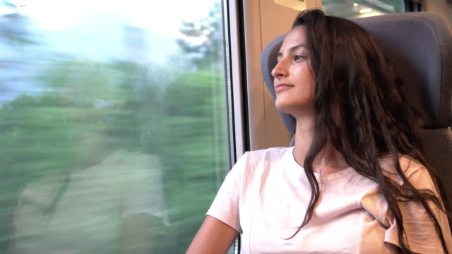 young beautiful woman traveling by train - ferrovia video stock e b–roll