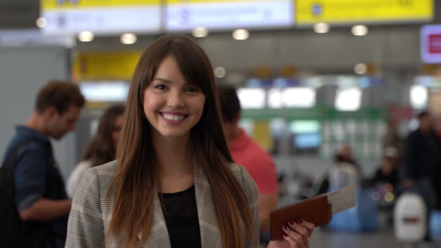 young beautiful woman traveling with friends walking up to camera smiling holding her passport and boarding pass - biglietto aereo video stock e b–roll