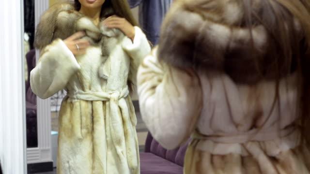 giovane bella donna cerca di vestiti al centro commerciale. - cappotto invernale video stock e b–roll