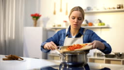 Young beautiful woman unhappy with cooking in kitchen, bored and tired of chores