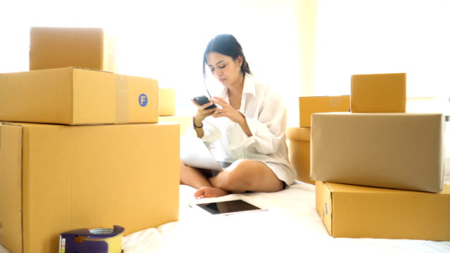 Young beautiful woman using a smartphone to do small business among the delivery box