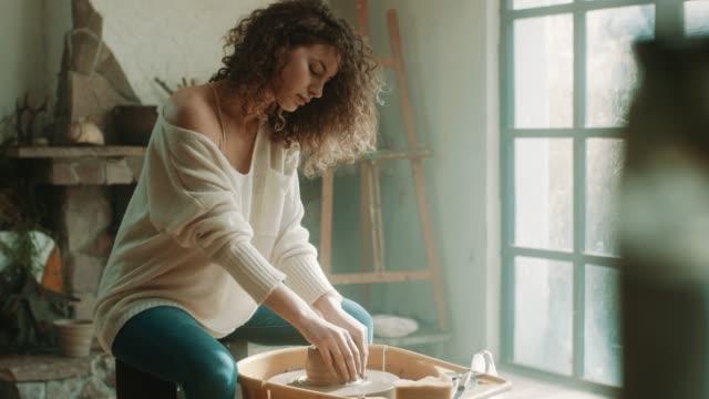 アトリエで陶器のホイールを使用して若い美しい女性 - 陶器点の映像素材/bロール