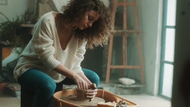 vídeos y material grabado en eventos de stock de mujer hermosa joven con rueda de alfarería en el atelier - rizado peinado